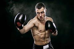 Boxeador tailandés muay del deportista que lucha en guantes en jaula del boxeo Aislado en fondo negro con humo Copie el espacio Imagenes de archivo