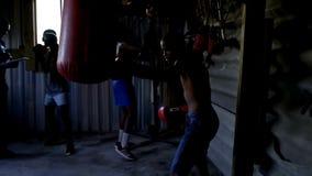 Boxeadores de sexo masculino que practican el encajonamiento con el saco de arena almacen de video
