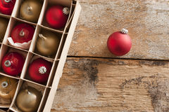 Boxed assortment or red and gold Xmas baubles. Boxed assortment or red and gold Christmas baubles with a single red one outside the packaging on a rustic wooden Royalty Free Stock Photography