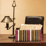 Boxed books with lamp. Books in an open box with a vintage lamp on a leather desk Stock Photography