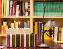 Boxed books with lamp and shelves. Books in an open box with a vintage lamp on a leather desk, and background with shelves full of books Royalty Free Stock Photo