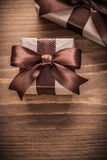 Boxed gift containers with brown ribbons on vintage wooden board Stock Image