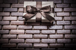 Boxed gift with ribbon on wooden wicker matting Royalty Free Stock Images