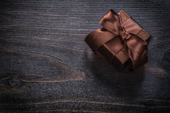 Boxed gifts with brown bows on vintage wood board Royalty Free Stock Photography