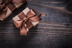 Boxed gifts with brown ribbons on vintage wood board Royalty Free Stock Images
