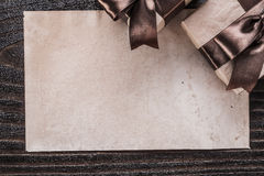 Boxed gifts with tied brown bows paper on wooden board Royalty Free Stock Image