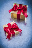 Boxed golden gift with red ribbon on scratched metallic backgrou Stock Photos