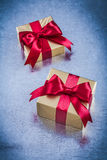 Boxed golden gifts with red bow on scratched metallic background Stock Photos