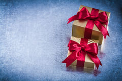 Boxed golden presents with red bow on scratched metallic backgro Stock Photos