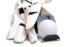 Boxed Golf Balls and Golf Glove. Open box of three premium golf balls.  The first ball has rolled out of the box.  A white golf glove lies across the top of the Stock Image