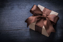 Boxed present with brown bow on vintage wood board copyspace Royalty Free Stock Image