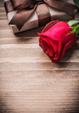 Boxed present expanded rosebud on wooden board Stock Photos