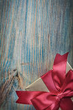 Boxed present in golden wrapping paper on vintage wooden board c Stock Images