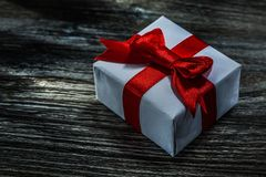Boxed present with red ribbon on wooden board.  royalty free stock image