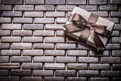 Boxed present with ribbon on wooden wicker matting Royalty Free Stock Photography