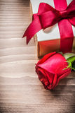 Boxed present with tied bow expanded rose on wooden board Stock Photo