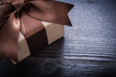 Boxed present with tied bow on vintage wooden surface Stock Photography