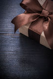 Boxed present in wrapping paper on vintage wood board copyspace Stock Image
