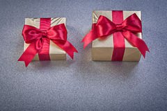 Boxed presents with red bows on grey background holidays concept Stock Photography