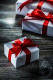 Boxed presents with red bows on wooden board.  royalty free stock image