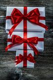 Boxed presents with red knots on wooden board.  royalty free stock photo