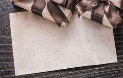 Boxed presents with tied brown bows paper on wooden board Royalty Free Stock Image