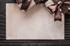 Boxed presents with tied brown ribbons paper on wooden board Stock Photography