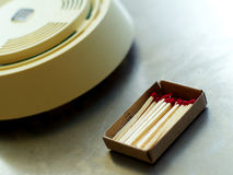 Boxed wooden matches and smoke detector. Boxed, red-tipped wooden matches on a shiny surface with a smoke detector in the background Stock Photos
