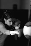 Boxeo agresivo del atleta de sexo femenino en gimnasio foto de archivo