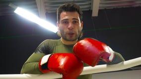Boxeo cansado del boxeador con el guardia de boca que descansa después del entrenamiento intensivo en club de la lucha Combatient almacen de metraje de vídeo