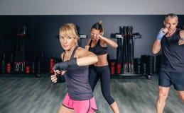 Boxeo de entrenamiento de la gente en un centro de aptitud Fotografía de archivo