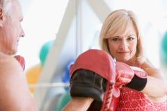 Boxeo de la mujer con el amaestrador personal en la gimnasia Fotos de archivo