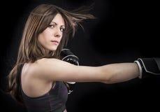 Mujer del boxeador durante el ejercicio del boxeo que hace golpe directo con negro Fotografía de archivo libre de regalías