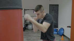 Boxeo masculino joven del boxeador como ejercicio para la lucha grande en un estudio del gimnasio para ganar la medalla de oro - almacen de video