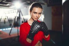 Boxeo moreno hermoso joven delgado apto de la mujer en ropa de deportes Luz oscuro oscura Imagenes de archivo