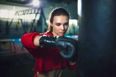 Boxeo moreno hermoso joven delgado apto de la mujer en ropa de deportes Luz oscuro oscura Fotografía de archivo libre de regalías