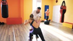 Boxeo que entrena en club de fitness Entrenamiento personal Un individuo grueso y un comienzo delgado de la muchacha a luchar Eje metrajes