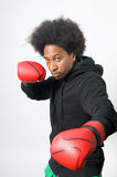 Boxer in attack. Black Boxer with red boxing gloves in attack Stock Photography