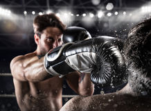 Boxer in a box competition beats his opponent. With a punch royalty free stock image