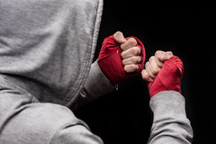 Boxer clenching fists. Rear view of boxer clenching fists wrapped with red tapes Royalty Free Stock Photos