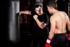 Boxer and coach training at a gym. Latin Boxer and his coach practicing some moves on a punching bag at a gym Royalty Free Stock Photography