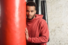 Boxer is concentrating before an important fight. Handsome athletic dark-skinned guy in a red sweatshirt is leaning on a punching bag in a gym. Boxer is stock photos