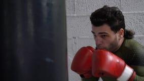 Boxer in den Boxhandschuhen, die Kampftasche am Kampftraining im Kampfverein treten Kämpfermanntraining durch Sandsack im Kasten