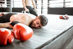 Boxer, der auf den Boden während eines boxenden Kampfes fällt stockfotografie