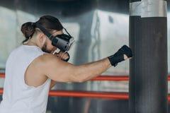 Boxer des jungen Mannes im Kopfhörertraining VR 360 für das Treten in Kampf der virtuellen Realität lizenzfreie stockfotos