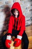 Boxer des kleinen Jungen mit Behandlung des blonden Haares in den tragenden Boxhandschuhen des roten Sweatshirts, die in einem St stockbilder