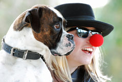 Boxer dog posing for photograph with happy pretty young woman owner. A beautiful portrait showing a pets perspective of a purebred Boxer breed dog sitting with stock photo