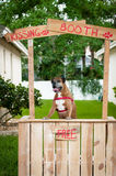 Boxer dog standing in a kissing booth. A boxer dog standing in a kissing booth awaiting customers Royalty Free Stock Photography