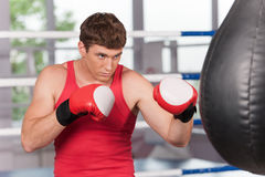 Boxer doing some training on punching bag at gym. Stock Photography
