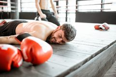 Boxer falling on the floor during a boxing battle. Beaten boxer lying on the floor during a boxing battle, having a knockdown on the boxing ring stock photography